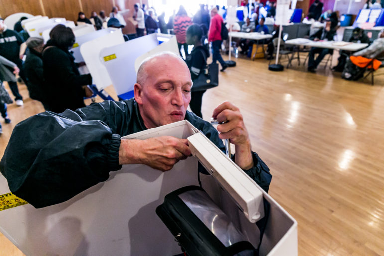 Martin Daniel Badonsky working to fix the light on a polling station at the community center auditorium located at 177 Dreiser loop in Co-op City.