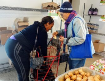 Cheryl Ware, a volunteer at the Bright Temple AME Church in Hunts Point, places food into a woman's cart at the church's weekly pantry.