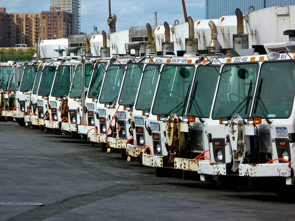 Department of Sanitation garbage trucks sit idle in a parking lot.