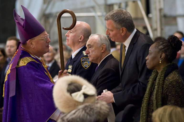 Mayor de Blasio, flanked by First Lady Chirlane McCray and Police Commissioner Bill Bratton and greeting Archbishop Timothy Dolan, attends Mass at St. Patrick's Cathedral the morning after the execution-style killing of two police officers.