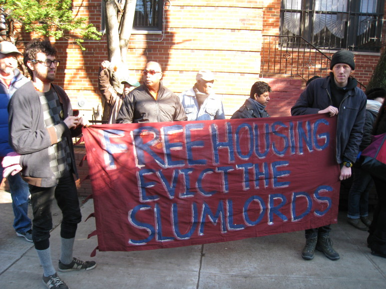"""All of the protesters were Latino with the exception of four young white men who had recently moved into the neighborhood, and are residents in a collective house known as """"Ma's House.""""  They held a sign that read """"Free Housing, Evict the Slumlords."""""""