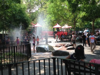 Children of Rayito De Luz Daycare cool off in the sprays of St. James Playground's water spouts after getting permission from caretaker Daniel Pena.