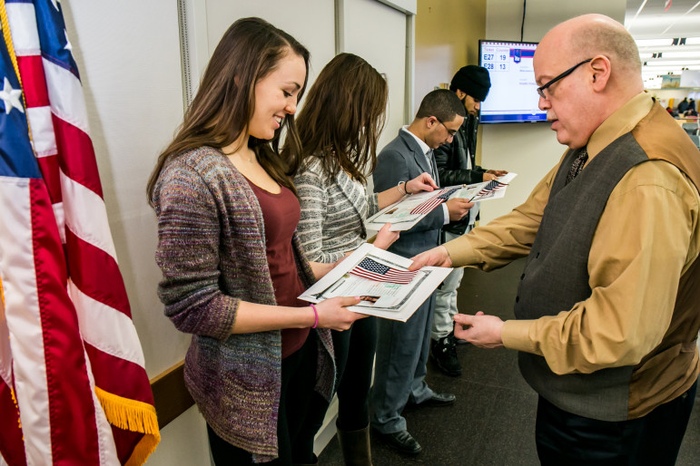 Supervisory Immigration Officer Joseph Mormino handing Sarah Siebes a certificate of citizenship as Sarah's twin sister Emma Siebes,  Rashed Alhanshali and Dario Cruz look on.