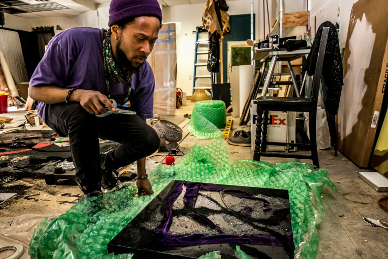 """During an afternoon in late February, artist Brandon Coley Cox preparing to to pack his painting titled """"Windows for Thornton"""" for an exhibition at Volta art fair in Manhattan. Mr. Cox has his studio at the Restoration Plaza in the Bedford-Stuyvesant section of Brooklyn, New York."""