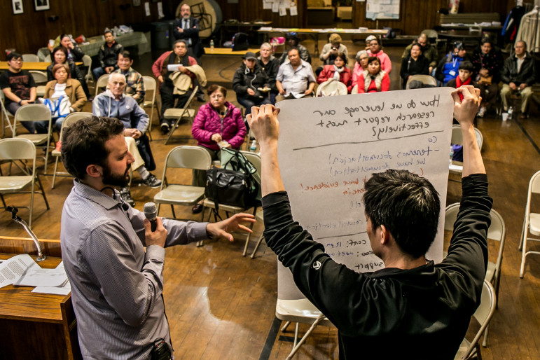 Andrew Hausermann, director of organizing at Faith in New York, speaks as James Hong, director of civic engagement at the MinKwon Center for Community Action assists at a meeting of the Flushing Rezoning Community Alliance in mid-April.