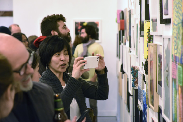 Patrons view artwork at Making History Exhibition and AiB 2015 Benefit, taking place at Storefront Ten Eyck Gallery, April 2015.