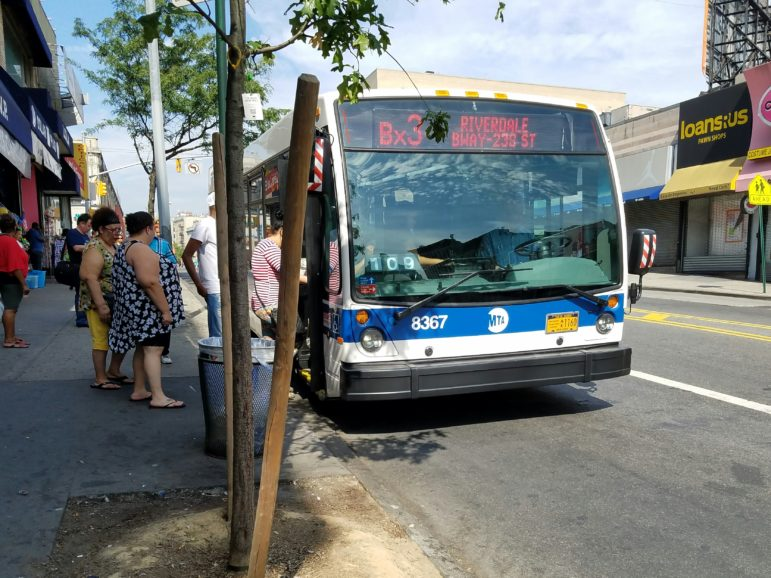 The Bx3 pulls up to the designated stop, and the waiting passengers board the bus and take an open seat.