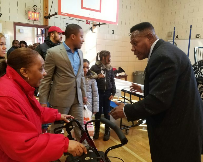 Poll workers Stevenson Nurse ushers the crowd of voters to each table, booth, and the exit.
