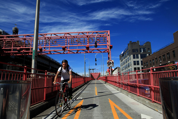 A cyclist crosses the Williamsburg Bridge.