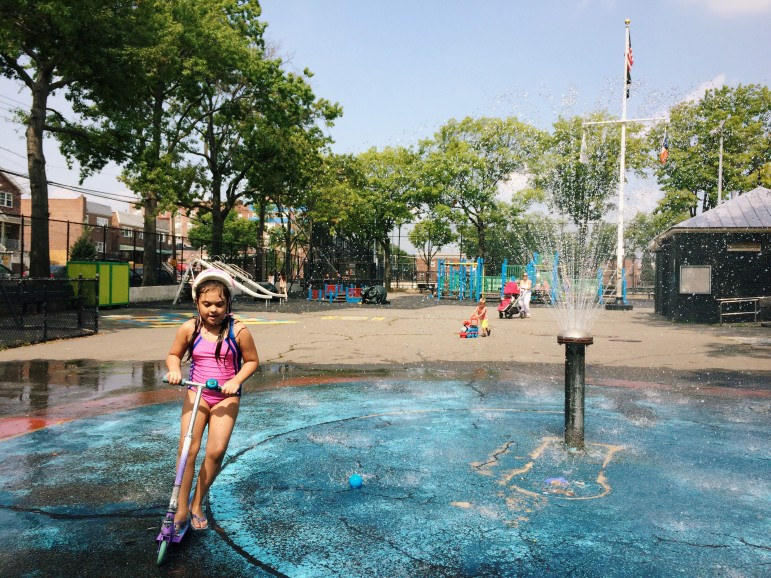 Scooting and splashing through the cooling spray at Loreto Playground.