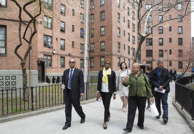NYCHA's Olatoye (center, with yellow scarf) at a 2014 tour of the Queensbridge Houses. One bright spot for NYCHA -- a new plan to extend the hours during which tenants can get service visits -- has become embroiled in a dispute with a labor union.