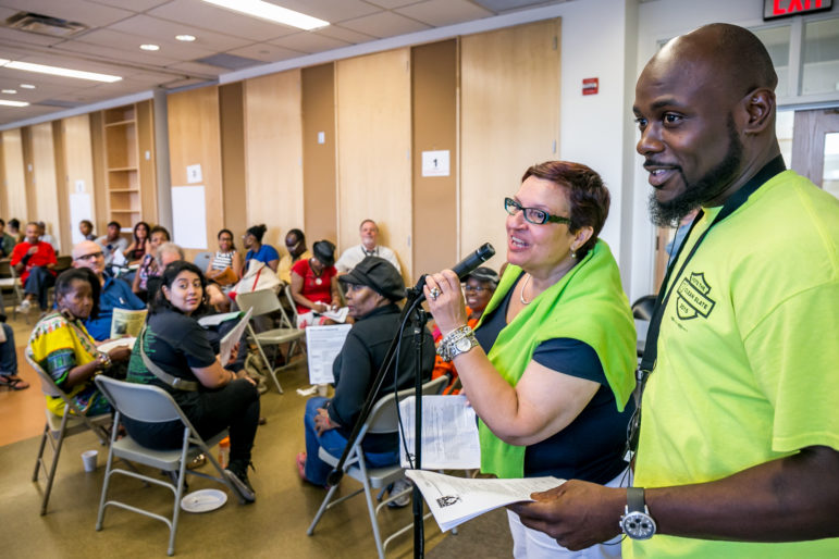Carmen Vega-Rivera, a tenant leader with Community Action for Safe Apartments, and Wayne Moten, a trade-union member and local resident, address an early August meeting about the pending Jerome rezoning.