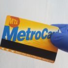 gloved hand holds metrocard